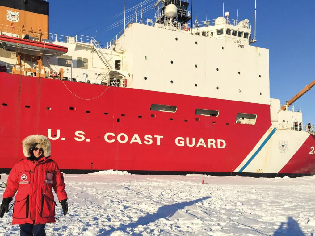 Michele Schallip stands in front of a U.S. Coast Guard ship wearing a red parka